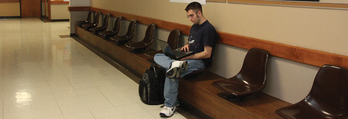 A student uses a laptop while waiting in the hallway